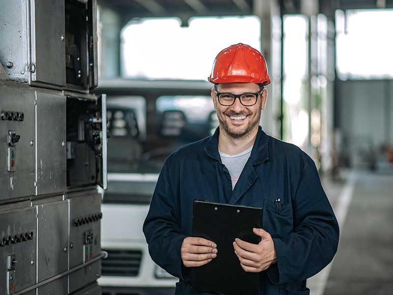 Warehouse worker smiling with clipboard